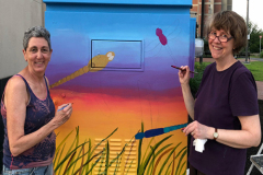 Karen McCarthy and Laurie Bogdan, in the process of painting the transformer box at Uncle Sam's Plaza.